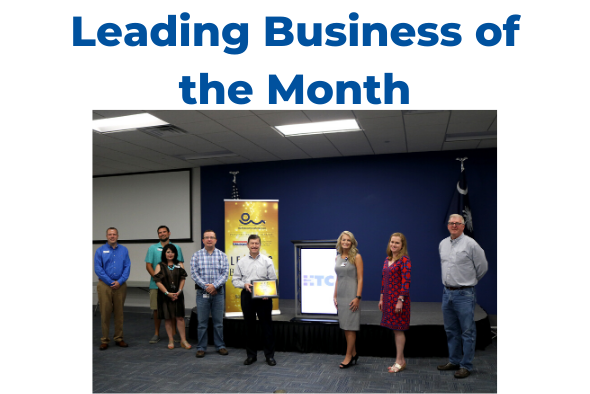 people standing in front of banner reading Leading Business of the Month