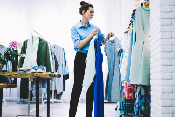 woman at clothing rack picking out items