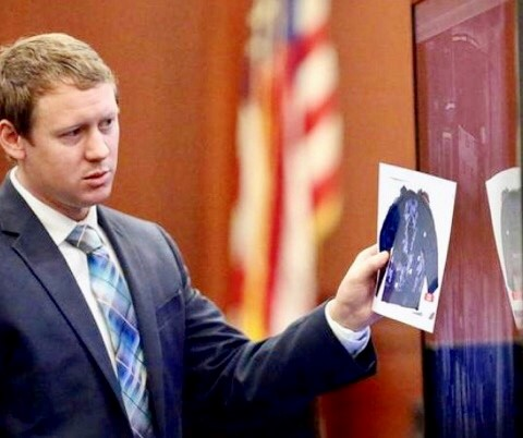 Photo of Josh Holford holding a piece of paper as a solicitor during a trial.